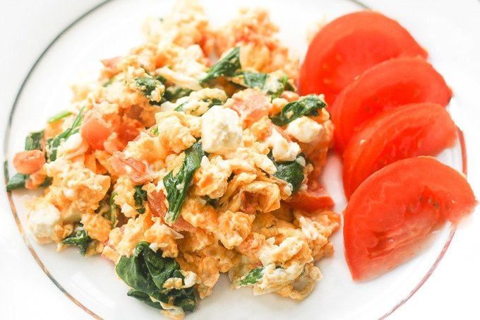 Healthy scrambled egg with spinach, tomato and feat